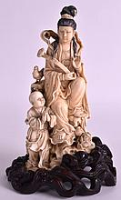 AN EARLY 20TH CENTURY CHINESE CARVED IVORY FIGURE OF GUANYIN Qing, modelled beside a child holding a rui. Ivory 6.75ins high.