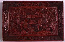 AN 18TH/19TH CENTURY CHINESE CARVED CINNABAR LACQUER RECTANGULAR TRAY Jiaqing, depicting three figures within an extensive landscape. 1ft 3ins x 10ins.