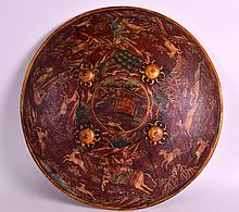AN EARLY 20TH CENTURY RAJASTHAN PAINTED LACQUER SHIELD depicting animals and figures within a landscape. 1Ft 6ins diameter.