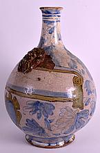 A 19TH CENTURY SOUTH EUROPEAN TIN GLAZED GLOBULAR BOTTLE with mask head mounts, painted with flowers and scrolls. 10.75ins high.