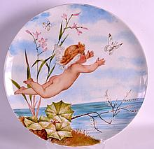 A LATE 19TH CENTURY MINTON ART POTTERY CHARGER painted with a nude winged cherub chasing butterflies. 1Ft 2ins diameter.