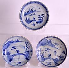 A SET OF THREE 18TH CENTURY CHINESE BLUE AND WHITE CA MAU CARGO SAUCERS with café au lait backing, painted with a fisherman upon a bridge. 4.25ins diameter.