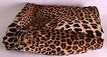 AN EARLY 20TH CENTURY LEOPARD SKIN BED COVER of na
