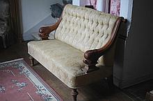 Banquette. Structure en bois tourné et accotoirs tête de dauphin. Garniture d'un tissu soyeux capitonné. Dim: l: 144 cm– L: 72 cm - P: 78 cm.