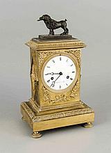 Klassizistische Kaminuhr um 1800, reliefiertes und vergoldetes Bronzegehäuse, bekrönt von vollplastischem Hund einen Brief in der Schnauze, seitlich Rautenapplikationen mit zeittypischen Elementen, emailliertes Zb. mit röm. Stunden und arab.