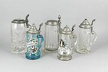 Konvolut von fünf Glaskrügen um 1900, mit Zinndeckeln und teilweise mit Kaltmalerei, der Größte und der Blaue mit durchgehendem Sprung, sowie ein weitere mit Sprung am Henkelansatz, H. 24 cm