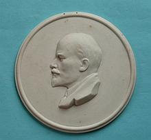 Vladimir Lenin: a circular bisque porcelain plaque moulded with a head in p
