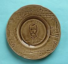 Tsar Nicolas II of Russia: a brown glazed pottery plate finely moulded with