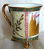 KPM Porcelain Scenic Commemorative Cup January 31, 1926Dated IANUVAR 31, 1926 (January 31, 1926); hand painted in gold, green and pink enamel; perhaps picturing the Cologne Cathedral and commemorating the final return to Germany of territory agreed