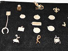 12 assorted charms and pins, 14 kt, 52 grams (Along with 3 not stamped or weighed)