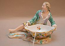 Meissen Porcelain Sweet Meat Dish man with coat.  Condition: good with minor normal wear.  Lth. 6 1/2