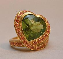 Gioielleria Nardi, St. Mark's Square, Venice Italy, hand crafted 20KT rose gold ring, center stone is a natural heart shape briolette cut peridot weighing 7.73 ct., surrounded by round brilliant cut orange sapphires with a total weight of 1.75 ct.