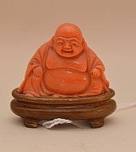 Carved coral buddha on wood stand, 1 7/8