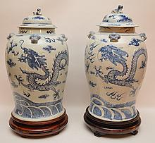 Pair Chinese Blue & White Jars & Covers with carved wood stands.  Condition: one has a repaired crack.  Ht. 17