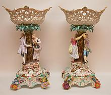 Pair Meissen Porcelain Compotes. Each with figural romantic scene and reticulated top. Condition: both have old repairs. One has a repairs to the man and woman's hands and each has what appears to be a repair where the stem meets the compote. Ht. 20