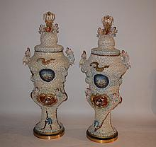 Pair Monumental Porcelain Urns.  Each has two scenes enclosed by flowers and figural bird, angel and woman decoration.  Ht. 5' 2