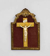 CRUCIFIX en ivoire représentant le Christ vétu d'un péplum. Il a été fixé sur une croix en bois doré et dans un cadre sculpté de coquilles et feuillages d'époque postérieure. XIXème siècle.