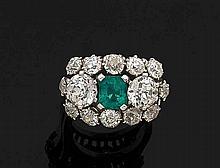Importante BAGUE en platine (850 millièmes) serti d'une émeraude rectangulaire taillée à degrés entourée de diamants taille ancienne dont deux plus importants.