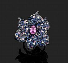 Belle BAGUE « fleur » en or noirci (750 millièmes) serti au centre d'un saphir rose de forme ovale entouré de pavages de saphirs bleus et roses ponctués de diamants taille brillant.