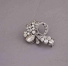 Broche nœud stylisé en platine (900 millièmes) et or gris (750 millièmes) ajouré, serti de diamants taille ancienne et demi taille, dont un plus important. Vers 1950. L: 4cm Poids brut: 13,2g. AC 9,4 X 5,8 = 3,10 carats environ. Fluo médium/