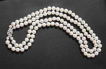 Collier de perles de culture de 8-9mm légèrement baroques sur deux rangs, et monté sur un fermoir cliquet avec sécurité en or gris à motif feuillagé, orné de diamants navettes, brillants et calibrés.
