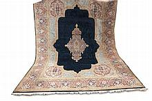 Orientteppich. Perser, groß. Florale, breite Bordüre mit großem Mittelstück auf blauem Grund. 20. Jh., ca. 390 x 260 cm. Leichte Gebrauchsspuren, etwas fleckig.