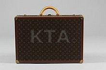 A Louis Vuitton hard-sided suitcase, with