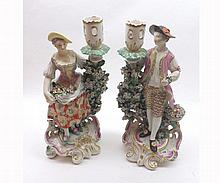 Pair of Derby Porcelain Candlestick figures of a flower seller and his female companion, each painted throughout in colours and encrusted with flowers on puce tinted and gilded scroll bases (his arm restored and her sconce and neck restored and