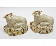 """Pair of Green & Co (Leeds) models of sheep and lambs, each decorated in ochre and brown and pale green, on a cream ground, (horns restored), 3 ½"""" high"""