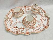 A Royal Crown Derby part Cabaret Set comprising two-handled oval large Tray, two Cups and Saucers, small Cream Jug and a further Teapot Lid, decorated throughout in iron red with a stylised floral design with gilded detail