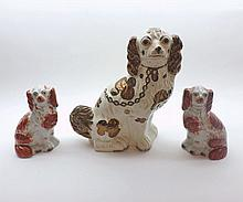 """A large 19th Century Staffordshire Copper Lustre decorated Model Spaniel, together with a pair of smaller liver and white Staffordshire Spaniels, largest piece 12"""" high (3)"""