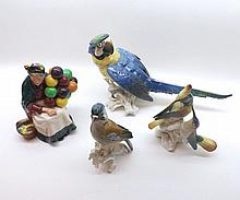 "A mixed lot comprising Royal Doulton model ""The Old Balloon Seller"", HN1316 (A/F) together with further Continental model Macaw, Jay and Humming Birds (A/F), largest piece 14"" long (4)"