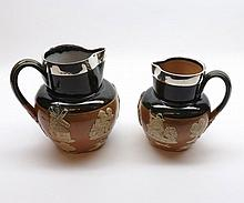 "Two Royal Doulton Stoneware Jugs decorated with raised sprigs and fitted with hallmarked Silver collars, largest 6 ½"" high (2)"