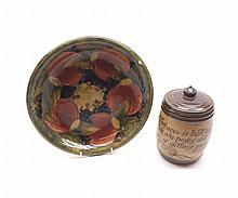 "A Mixed Lot comprising: a William Moorcroft Pomegranate pattern circular Dish (edge chip and crazing throughout), 9 ¾"" wide; together with a Doulton Lambeth Stoneware Tobacco Jar, decorated with rows of text (2)"