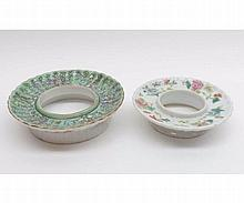 """Two Oriental Circular Stands, one painted in famille rose and the other in famille rose, pale blue etc on a celadon ground, the outer rim in iron red with palm trees, 4 ½"""" and 5 ¼"""" diameter"""