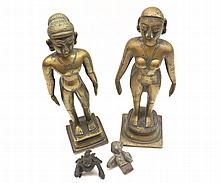 Two Oriental Gilded Bronze Figures of a male with a chain around his neck and a pendant, and his knees incised with devices, female also decorated with chain and pendant etc, together with small bronzed kneeling mythological figure and further base