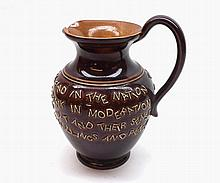 "A Doulton Lambeth Stoneware Motto Jug decorated with lines of text on a brown background, 6"" high"