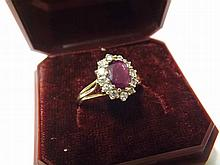 A late 20th Century hallmarked 18ct Gold Ring, central oval Ruby surrounded by twelve small Brilliant Cut Diamonds