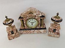 A late 19th Century variegated pink Marble garniture timepiece, the architectural case with free standing columns and plinth base to a spun Brass bezel enclosing an Arabic enamel dial with outside minute track and Fleur de Lys type hands to a single