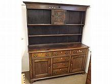 """Early 19th Century Oak Dresser, the base with six short drawers and two panelled doors raised on bracket feet, the back piece with three shelves and central door with carved floral decoration, 67"""" wide"""