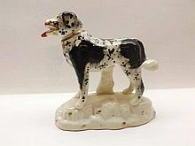 A 19th Century Staffordshire Model of a black and white dog, raised on plin