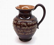 A Doulton Lambeth Stoneware Motto Jug decorated with lines of text on a bro