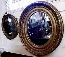 A large Gilt and Gesso Oval Wall Mirror with a fo