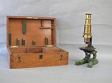 Brass microscope in mahogany case with extra