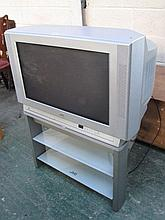Modern JVC TV on stand with shelf and remote