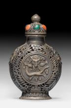 A PARTLY OPENWORK SILVER SNUFFBOTTLE DECORATED WITH DRAGON HEADS.