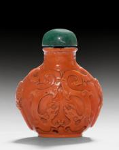 A CORAL RED GLASS SNUFF BOTTLE DECORATED WITH DRAGONS IN RELIEF.