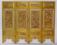 FOUR-PART CARVED AND OPENWORK WOODEN FOLDING SCREEN PAINTED IN GOLD LACQUER.