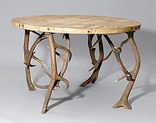 A CIRCULAR TABLE WITH ANTLER LEGS,Alpine region.