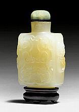 SNUFFBOTTLE MIT CHILONG-RELIEF. China, H 6,5 cm.Hellseladonfarbene Jade mit gelblichen Einschlüssen. Quaderförmig mit beringten Maskarons auf den Schmalseiten und archaisierenden Chilong-Reliefs auf den Schauseiten. Jadeitstopper. Holzstand. Min.